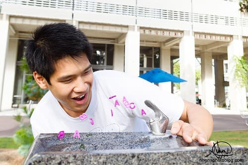 """Kevin Huynh drinking from Michael Asher's Untitled fountain, rumored to grant """"A""""s if sipped from before taking a midterm. Photo courtesy of Nhan Nguyen."""